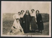 1912 A Sister and Students Standing on a Road in Front of a Field